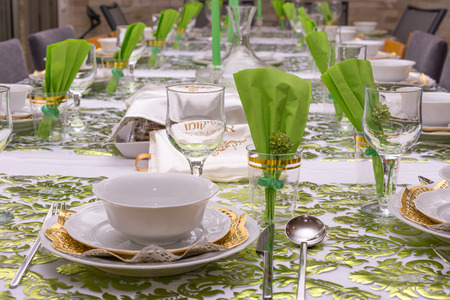 Modern Passover Seder table with green  and gold decorations in Tel Aviv, Israel, complete with Matzos and a traditional Seder Plate.  Matzo cover reads Afikoman in Hebrew. Stock Photo