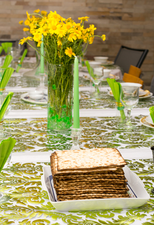 Matzos on a Modern Passover Seder table with green  and gold decorations in Tel Aviv, Israel Stock Photo