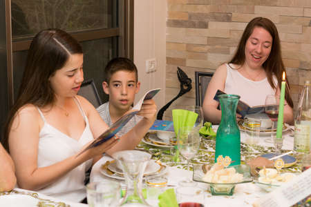 matzah: TEL AVIV - APRIL 10, 2017: Modern secular Israeli family (two sisters and a brother) sitting together for a traditional Passover Seder dinner