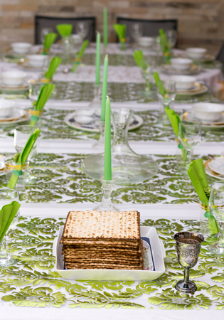 matzah: Modern Passover Seder table with green  and gold decorations in Tel Aviv, Israel, complete with Matzos and a silver wine goblet.