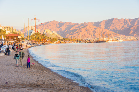 EILAT, ISRAEL - DEC. 29, 2016: People on vacation enjoying the sunset at the  Red Sea beach of sunny Eilat, Israel