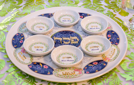 Traditional Passover plate saying Passover in Hebrew with six small dishes for Passover condiments on a Seder table in Tel Aviv, Israel