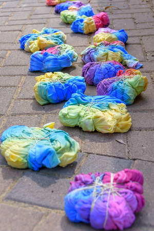 Still-wet tie-dye T-shirts compressed with rubber bands after being painted by a group of teenagers in a tie-dye party