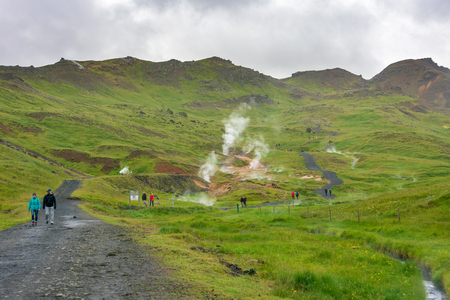 GOLDEN CIRCLE, ICELAND - JULY 30, 2018: Tourists hiking the Hengilssvaedid hot springs trail near Reykjavik in the Golden Circle of Iceland.  The climb features panoramic views and natural hot springs