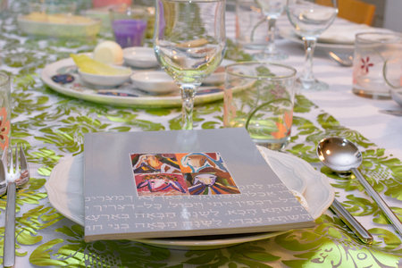 Modern Passover Haggadah on a Seder table with green  and gold decorations in Tel Aviv, Israel