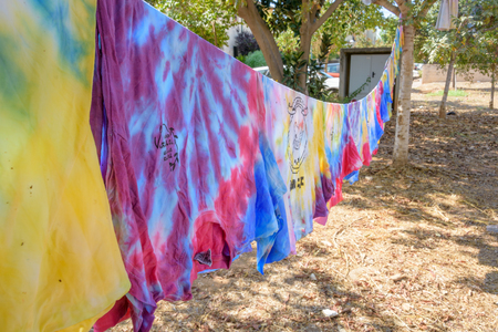 TEL AVIV, OCT. 13, 2017: Still-wet tie-dye T-shirts hanging on a cloth line after being painted by a group of teenagers in a tie-dye party