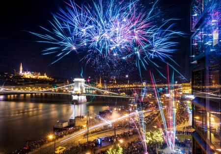BUDAPEST - JAN. 1, 2020: Happy people celebrating the New Year and new decade on the Danube in Budapest with lots of fireworks at midnight. Imagens