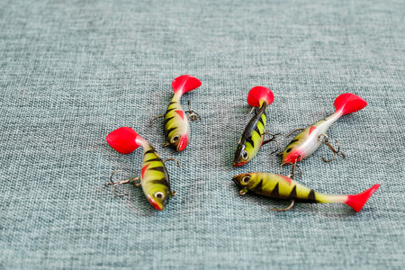 Silicone bait. Twisters on the background of burlap. Lures with triple hooks in the form of a small perch. Red tail. Stock Photo