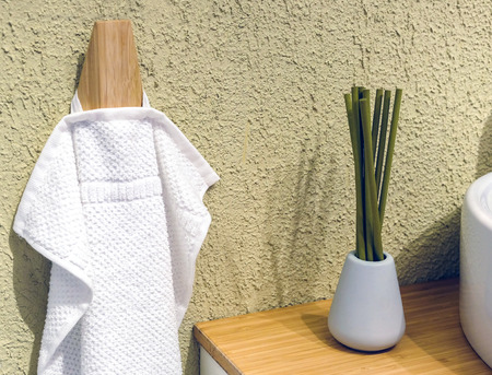 Clean Colored towels hanging on the rack in the bathroom. Focus on the top of the hook and towels