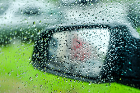 Water drops or rain drops on the car glass. Blurred background. Flank. Car mirror. Banco de Imagens