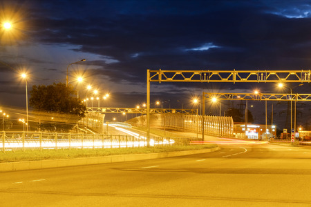 Night shooting of the road. At night the city lights up. Lighting of the motorway. Plumes of headlights of cars