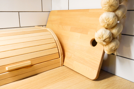 Bread bin. View of the kitchen counter with cutting Board, hanging on the wall a few heads of garlic.