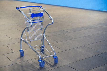 Small empty food basket trolley with child seat.