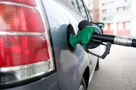 man pumping gasoline fuel in car at gas station-transportation and ownership concept Stockfoto