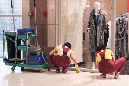 Image of the cleaners at the Mall. Two women wipe stains on the floor. Tools nearby
