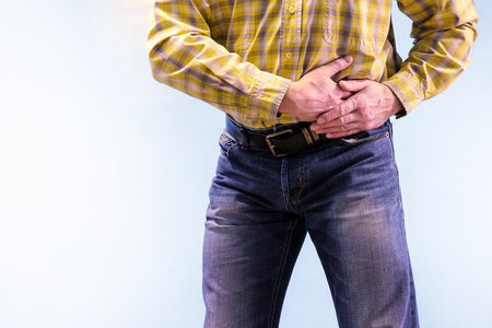 Urolithiasis. Chronic pancreatitis. Stones in the urine. The man grabbed his groin in a fit of pain