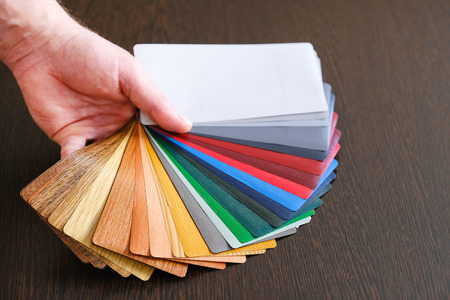 Samples of lamination deployed, the master holds in his hand. On a wooden background for lamination of any wooden and plastic products used in construction