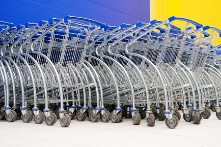 Baskets on wheels. Parking baskets for buyers of supermarkets and hypermarkets