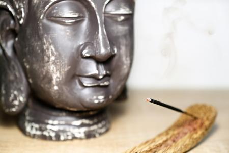 Buddha head statue, hand-made handicraft. Incense in the stand Banco de Imagens