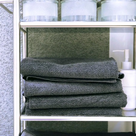 Clean colored towels hanging on the hanger in the bathroom. Towels are hung on hooks.