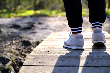 Jogging in sneakers on the bridge in the Park. Sport, Health and physical culture concept