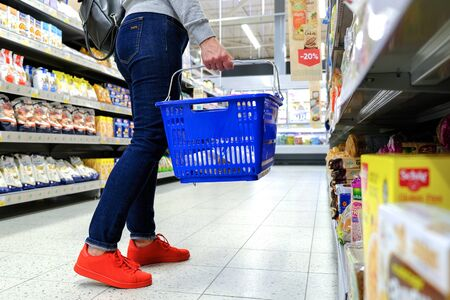 A woman holds the handle of the grocery cart, going down the aisle in the supermarket. Buy the product. Saint-Petersburg. Russia. 05 20 2019