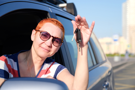 The beautiful girl became the happy owner of the new car. Holds keys in his hands smiling to squinting from the sun