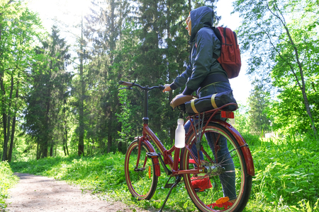 The girl smiles happily. Riding in the Park on a Bicycle path. Face exposed to sunlight