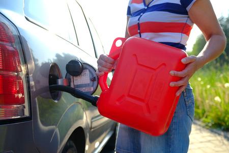 Zwangsstopp. Im Tank des Autos ging das Benzin aus. Eine Frau füllt das Auto mit Benzin aus einem Reservetank. Kanister mit 10 Litern