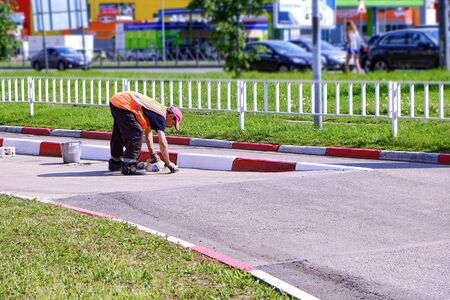 Man working. Repaints with a brush the road concrete limiter in road coloring Reklamní fotografie