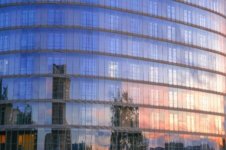Modern multi-storey building with a glass facade. The evening sunset sky is reflected in the Windows of the facade