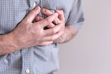 The young man is suffering from chest pain. Chest spasm, angina pectoris. Heart attack Reklamní fotografie