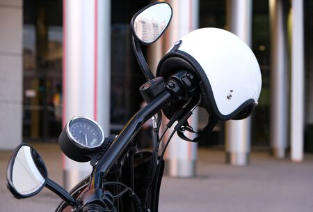 The throttle and brake on the handlebars of the motorcycle with chrome and white helmet without a visor. A white helmet hanging on the handle of the motorcycle