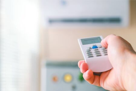 Remote control. Male hand with air conditioning remote control. The man switches the modes of conditioning. Regulates the cooling temperature of the room