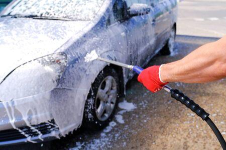 Man pours active foam car body. Car wash. Self-service washing complex. High pressure car wash