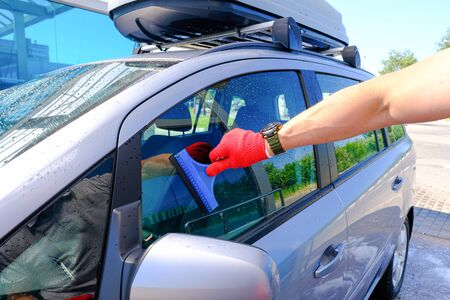 A man with a rubber scraper removes the remains of water from the glass after washing the car. Car wash. Self-service washing complex. High pressure car wash Reklamní fotografie