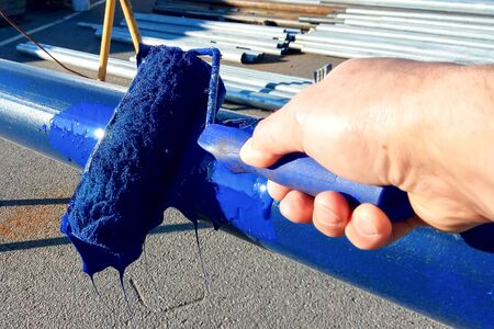 Worker paints steel pipe with roller to prevent rust. Blue paint