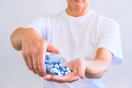 The woman poured a handful of sports capsules into the palm of her hand. Reception before training. Increase strength and energy. Fat burning and weight loss