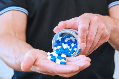 The man poured a handful of sports capsules into his palm. Reception before training. Increase strength and energy. Fat burning and weight loss