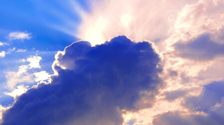 The cloud covered the sun. Halo of sunlight. Blue sky with clouds. Natural background. Warm summer season