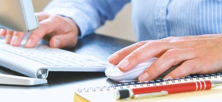 Bureau avec ordinateur et clavier en arrière-plan. Le carnet et le stylo sont préparés pour les dossiers de travail