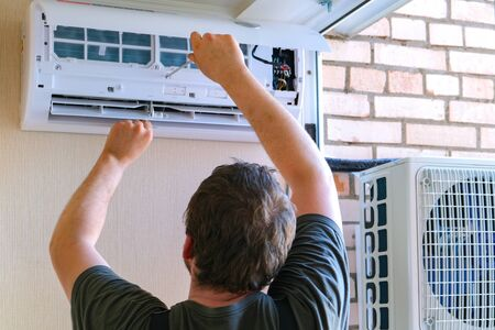 Male technician repairing air conditioner outdoors