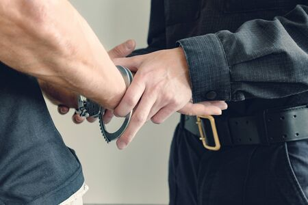 Buttons COP handcuffs an arrested criminal. The man at the police station. Handcuffs on the wrists of the detained man