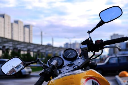 Evening. Throttle and brake on the handlebar of the motorcycle with chrome rear-view mirrors. Against the twilight sky