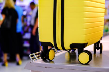 Airport, yellow suitcase with wheels on the counter. In the background people at the front Desk. Soft focus Archivio Fotografico - 129200286