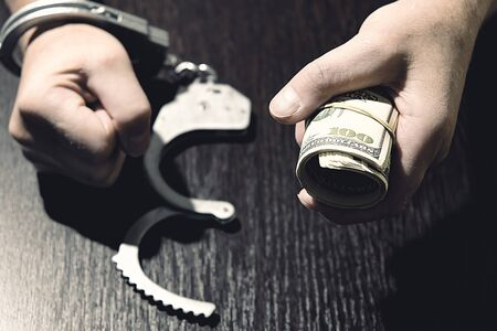 Handcuffed hands clenched into a fist. A wad of dollars tied with a rubber band