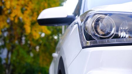 Car front view close-up on the background of a Park alley. Headlight glass. Background design. Detail of modern car headlights