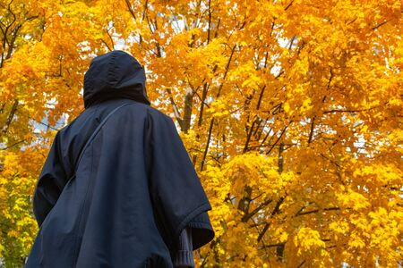 Silhouette of a girl in a Cape in the autumn Park. For Wallpaper design. Abstract orange background. Autumn forest. The natural pattern