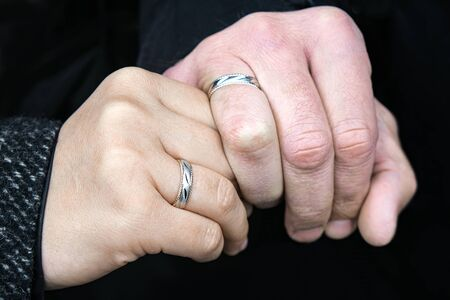 Wedding rings on his hands. An elderly couple got married. Happy family. Family outdoors