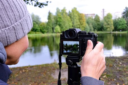 Girl photographer. The tripod with the camera